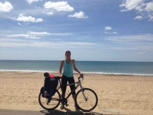 A photo of Emma Brown, physiotherapist with Central Health Physiotherapy, with her bicycle on the beach