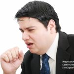 A picture of a businessman coughing