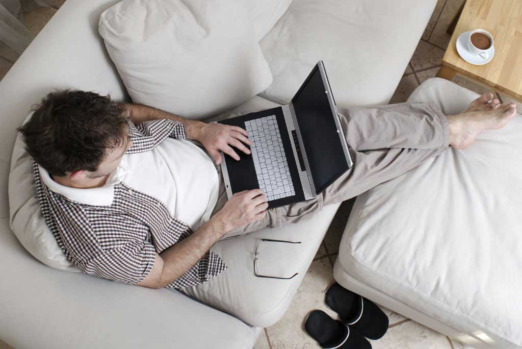 Man sitting on sofa with laptop on his lap