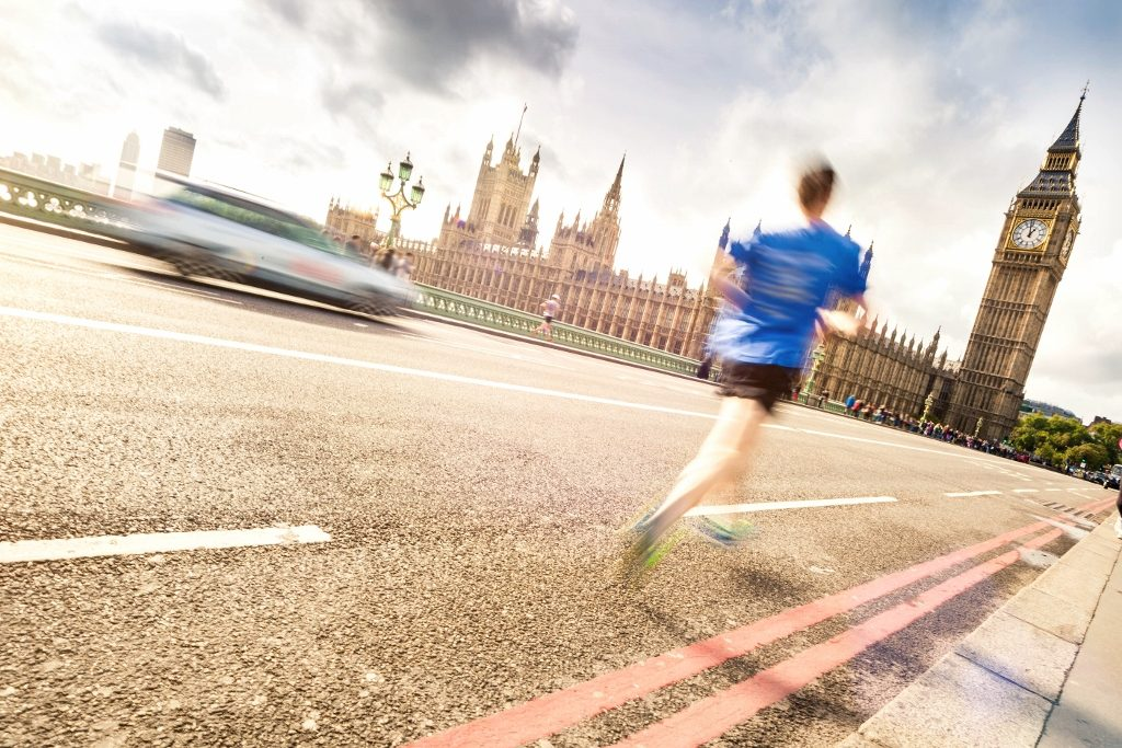 A person jogging across the bridge the Houses of Parliament in the background