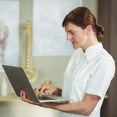 physiotherapist holding laptop for video appointment